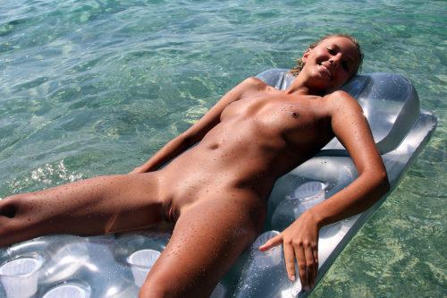gola devojka na dušeku pluta na vodi