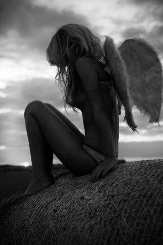 žena sa krilima anđela sedi na steni
